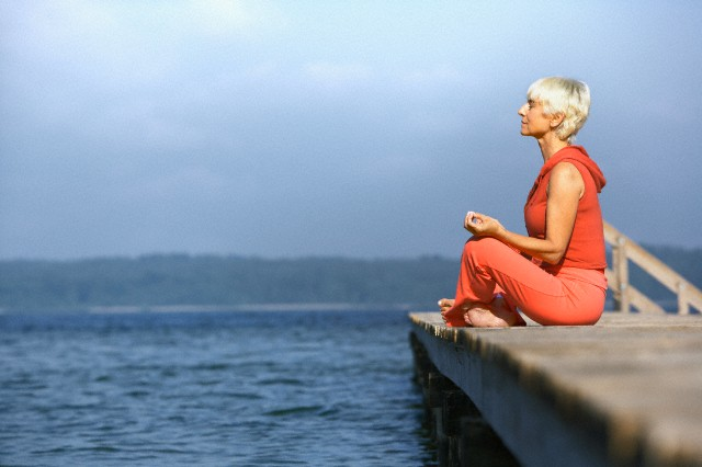 Senior woman practicing yoga on jetty