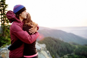 Man and woman embrace on cliffs edge in the early morning
