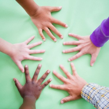 Close up of children's (8-9) hands on green background
