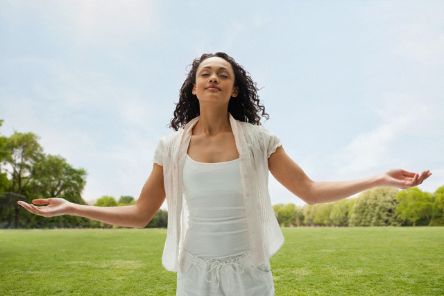 Mixed race teenage girl in field with arms outstretched