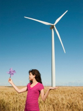 USA, Oregon, Wasco, Girl (13-15) holding fan in wheat field in front of wind turbines
