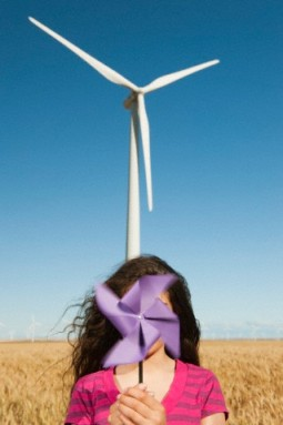 USA, Oregon, Wasco, Girl (13-15) holding fan n front of wind turbines