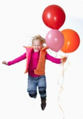 Girl (8-9) with multi-color balloons jumping, portrait