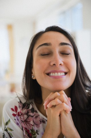 Smiling Caucasian woman with hands clasped